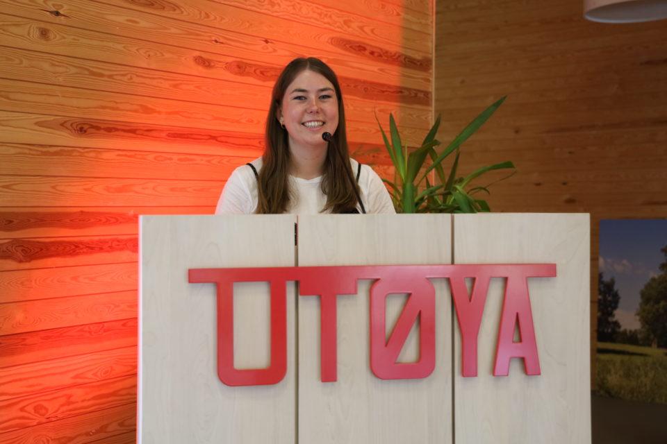 Leder av AUF Astrid Willa Hoem har et stort smil og står på en talerstol med skriften Utøya