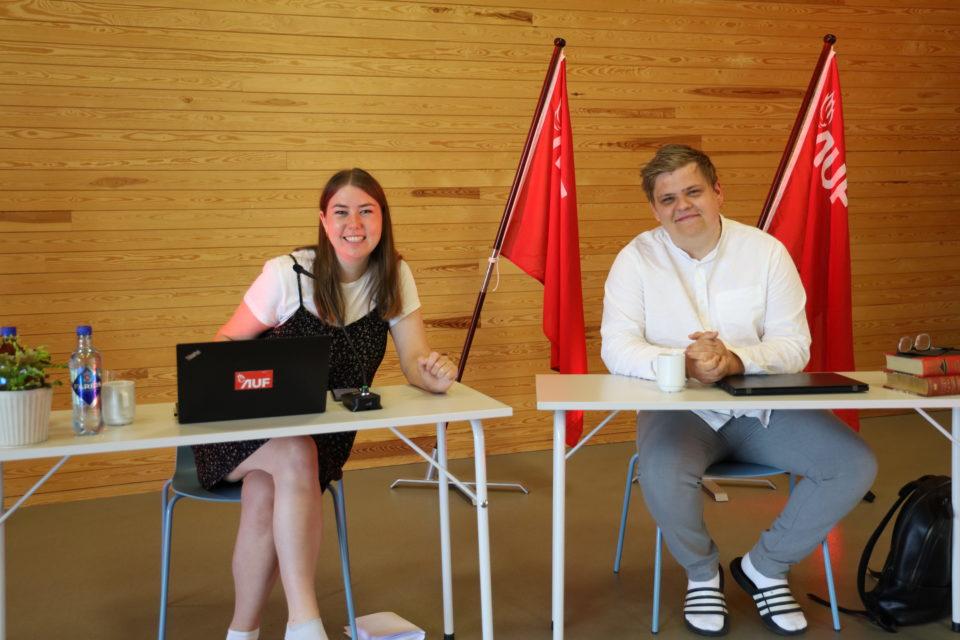 Astrid og Gaute sitter bak hvert sitt bord og smiler